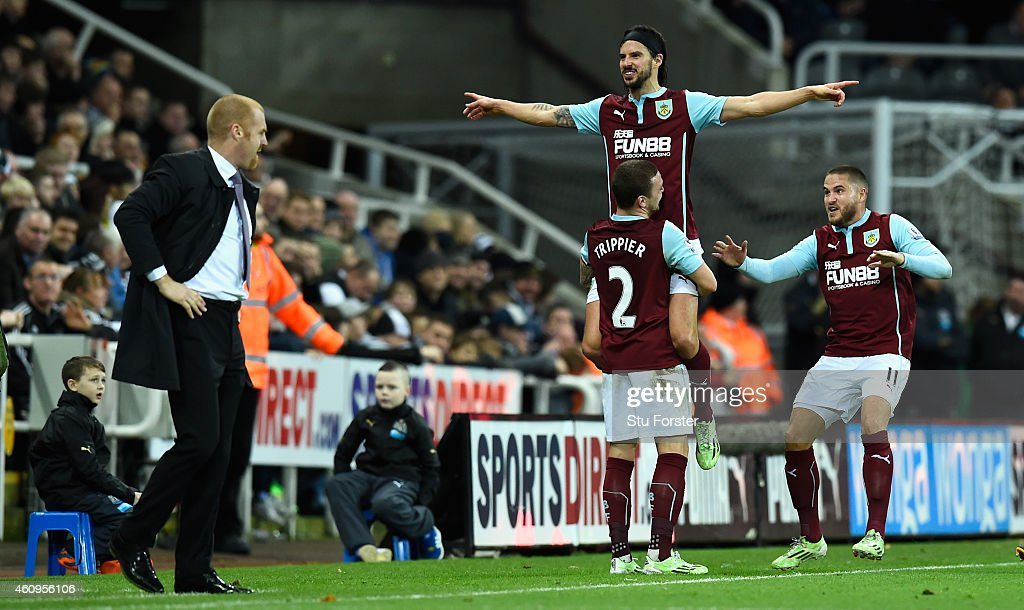 George Boyd of Burnley is lifted up after scoring the third Burnley goal as manager Sean Dyche (l) looks on during the Barclays Premier League match between Newcastle United and Burnley at St James' Park on January 1, 2015 in Newcastle upon Tyne, England.