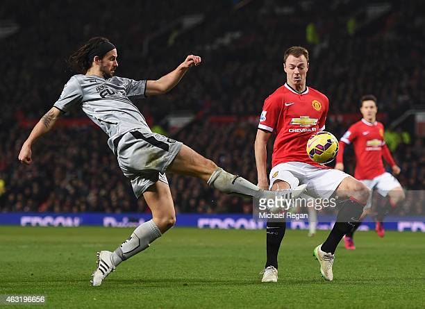 George Boyd of Burnley shoots as he is closed down by Jonny Evans of Manchester United during the Barclays Premier League match between Manchester...