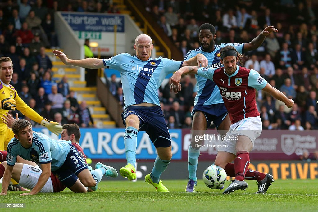 George Boyd of Burnley shoots past James Collins of West Ham to score his team's first goal during the Barclays Premier League match between Burnley and West Ham United at Turf Moor on October 18, 2014 in Burnley, England.