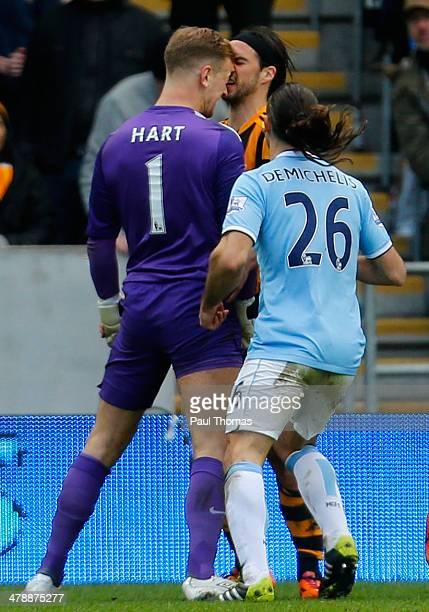 George Boyd of Hull City clashes with Joe Hart of Manchester City during the Barclays Premier League match between Hull City and Manchester City at...