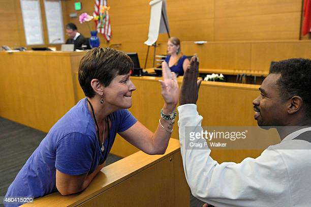 George Brady gets a high five from Shari Lewinski program administrator of behavioral health courts during the Court to Community special docket at...