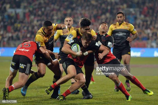George Bridge of the Crusaders is tackled during the round 12 Super Rugby match between the Crusaders and the Hurricanes at AMI Stadium on May 13...