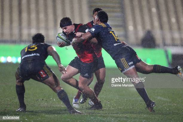 George Bridge of the Crusaders tries to break through the tackle of Waisake Naholo of the Highlanders during the Super Rugby Quarter Final match...