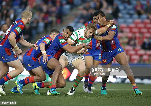 George Burgess of the Rabbitohs is tackled by the Knights defence during the round 25 NRL match between the Newcastle Knights and the South Sydney...
