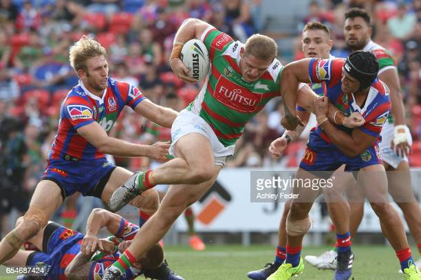 George Burgess of the Rabbitohs is tackled by the Knights defence during the round three NRL match between the Newcastle Knights and the South Sydney...