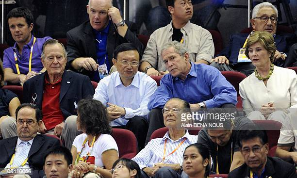 George Bush with his wife Laura and father George HW Bush during the men's preliminary basketball match at the Olympic Basketball Gymnasium in...