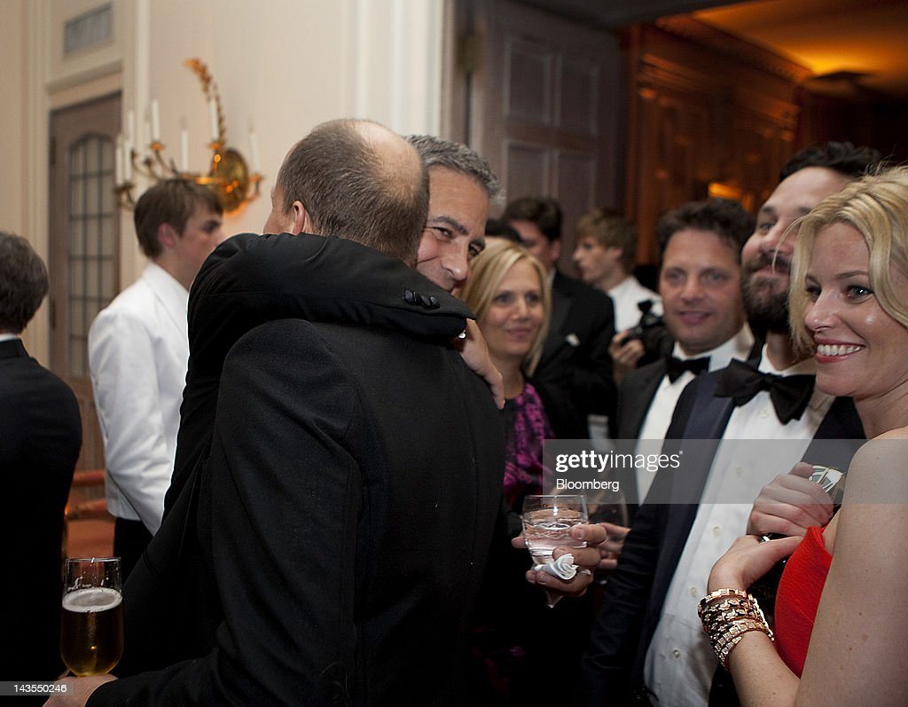 George Clooney, left, hugs Woody Harrelson, as Paul Rudd, second from right, and Elizabeth Banks, right, look on at the Bloomberg Vanity Fair White House Correspondents' Association (WHCA) dinner afterparty in Washington, D.C., U.S., on Saturday, April 28, 2012. The 98th annual dinner raises money for WHCA scholarships and honors the recipients of the organization's journalism awards. Photographer: Joshua Roberts/Bloomberg via Getty Images