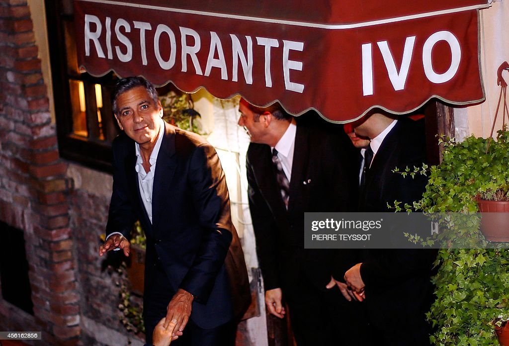 George Clooney looks on as he leaves the restaurant Da Ivo with friends and his father during his stag night event in Venice on September 27 2014...