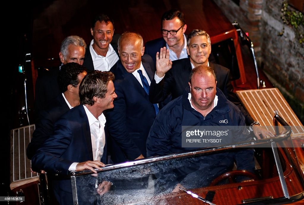 George Clooney waves to his fans waves as he leaves the restaurant Da Ivo with friends and his father during his stag night event in Venice on...