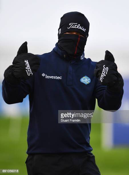 George Coetzee of South Africa gives a thumbs up as he attempts to keep warm during day one of the Nordea Masters at Barseback Golf Country Club on...