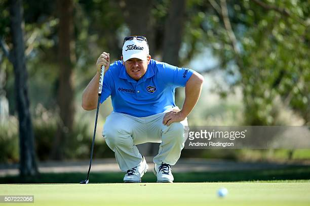 George Coetzee of South Africa lines up a putt on the 1st green during the second round of the Commercial Bank Qatar Masters at the Doha Golf Club on...