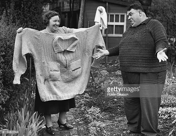 George Cook a petty officer with the Royal Navy shrugs his shoulders as his sister holds up a sweater sent to him by the Newfoundland War Committee...