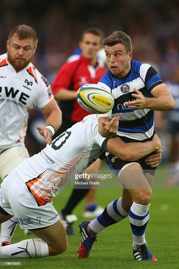George Ford of Bath feeds a pass as Dan Biggar of Ospreys holds on during the Pre season match between Bath and Ospreys at the Recreation Ground on...