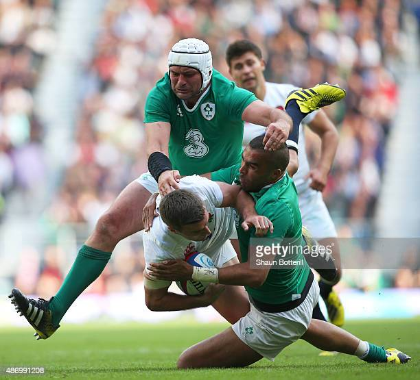 George Ford of England is hauled down by Simon Zebo of Ireland and Rory Best of Ireland during the QBE International match between England and...