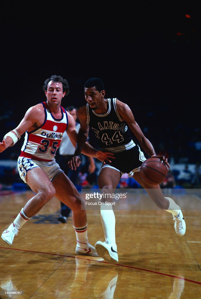 George Gervin of the San Antonio Spurs drives on Kevin Grevey of the Washington Bullets during an NBA basketball game circa 1982 at the Capital...