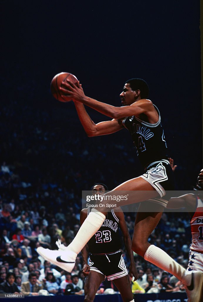 George Gervin of the San Antonio Spurs drives to the basket against the Washington Bullets during an NBA basketball game circa 1984 at the Capital...