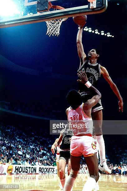 George Gervin of the San Antonio Spurs dunks over Robert Reid of the Houston Rockets during a game played in 1984 at The Summitt in Houston Texas...