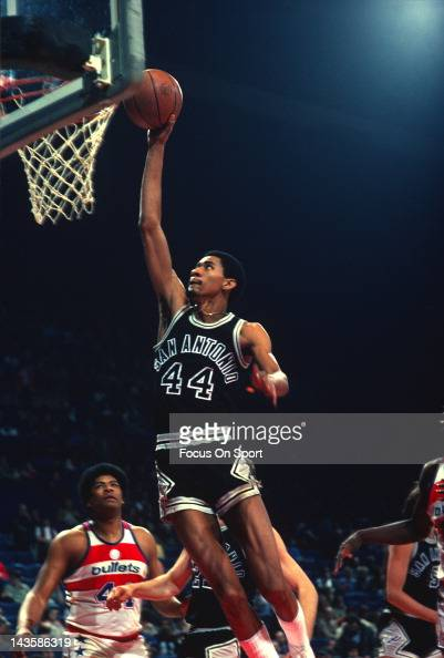 George Gervin of the San Antonio Spurs goes up to jam the ball against the Washington Bullets during an NBA basketball game circa 1982 at the Capital...