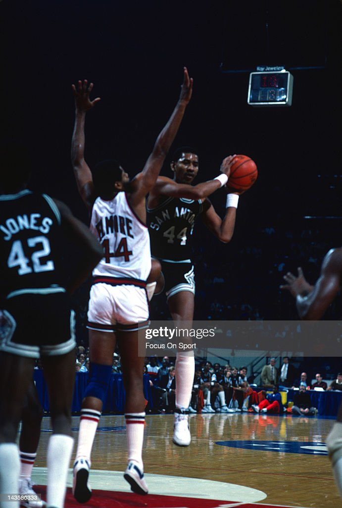 George Gervin of the San Antonio Spurs looks to pass over Len Elmore of the New York Knicks during an NBA basketball game circa 1983 at the Capital...