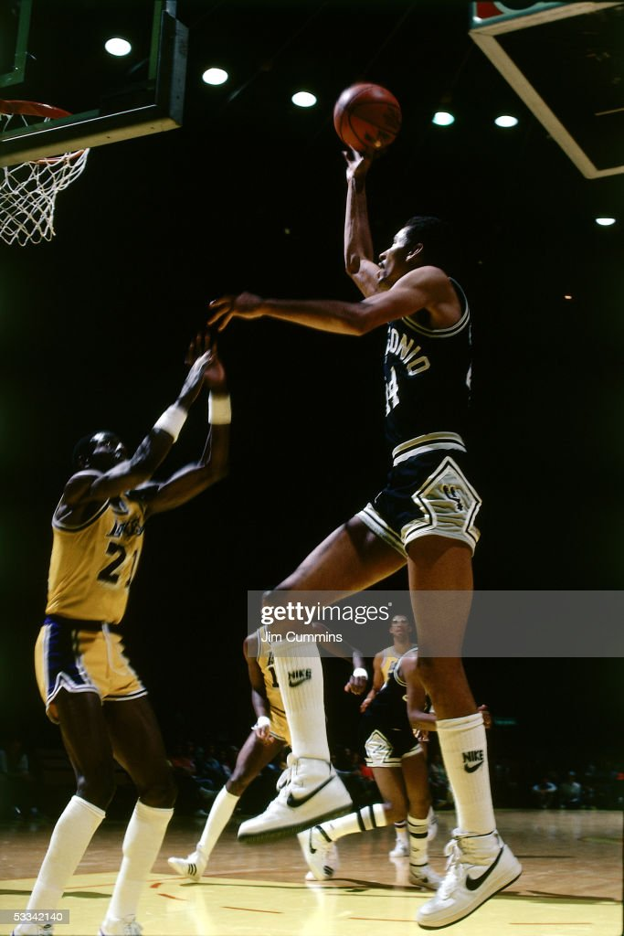 George Gervin of the San Antonio Spurs shoots a jumpshot along the baseline against Michael Cooper of the Los Angeles Lakers during an NBA game circa...
