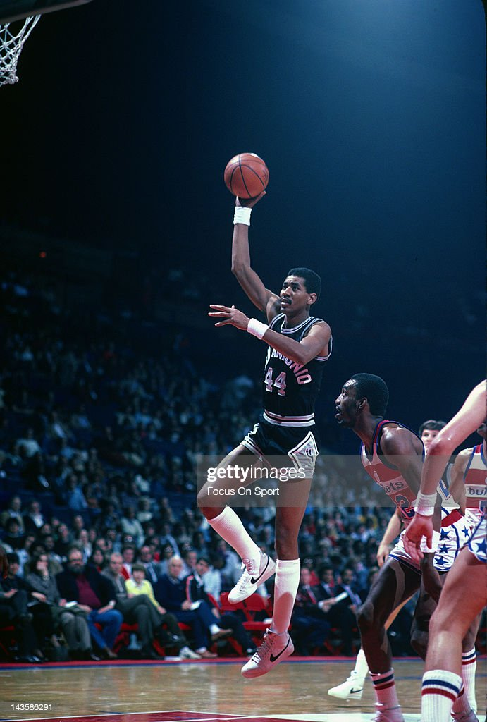 George Gervin of the San Antonio Spurs shoots over Don Collins of the Washington Bullets during an NBA basketball game circa 1982 at the Capital...