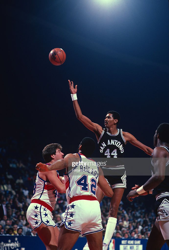 George Gervin of the San Antonio Spurs shoots over Jeff Ruland and Greg Ballard of the Washington Bullets during an NBA basketball game circa 1982 at...