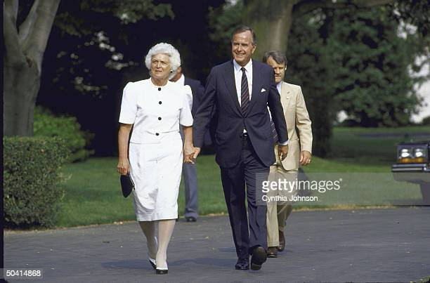 George H W Bush walking with his wife with secret servicemen following at Boston Pops concert on WH south lawn