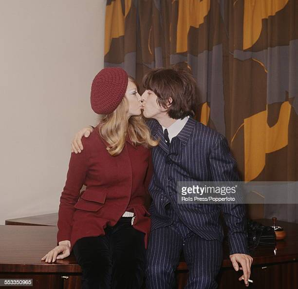 George Harrison guitarist with the Beatles kisses his wife Pattie Boyd at a press conference in London on 22nd January 1966 to announce the news of...
