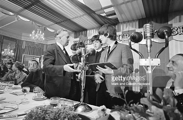 George Harrison of the Beatles accepts his award from British Labour Leader of the Opposition Harold Wilson at the Variety Club of Great Britain...