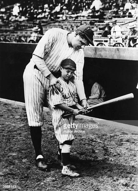George Herman Ruth known as 'Babe' Ruth American baseball player showing a youngster how to hold a basesball bat in Yankee Stadium
