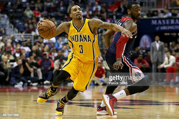 George Hill of the Indiana Pacers dribbles past John Wall of the Washington Wizards in the second half at Verizon Center on March 25 2015 in...