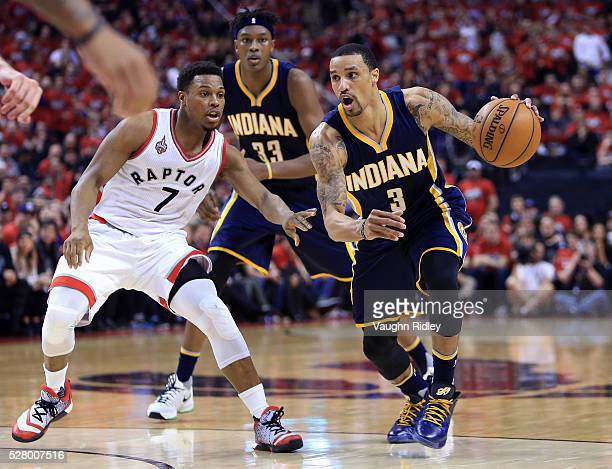 George Hill of the Indiana Pacers dribbles the ball as Kyle Lowry of the Toronto Raptors defends in the first half of Game Seven of the Eastern...