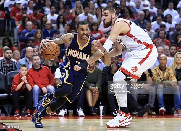 George Hill of the Indiana Pacers drives against Jonas Valanciunas of the Toronto Raptors in the first half of Game Seven of the Eastern Conference...