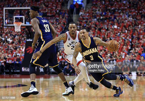 George Hill of the Indiana Pacers drives against Norman Powell of the Toronto Raptors in the first half of Game Seven of the Eastern Conference...