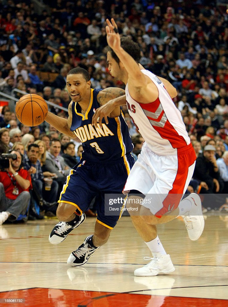 George Hill #3 of the Indiana Pacers drives to the net past Jose Calderon #8 of the Toronto Raptors on October 31, 2012 at the Air Canada Centre in Toronto, Canada.