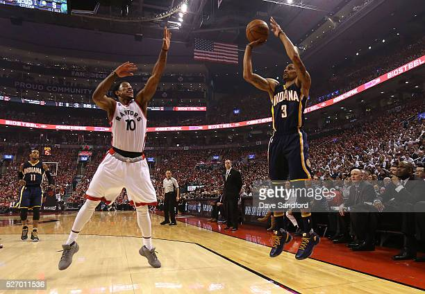 George Hill of the Indiana Pacers shoots for a three point basket against DeMar DeRozan of the Toronto Raptors in Game Seven of the Eastern...