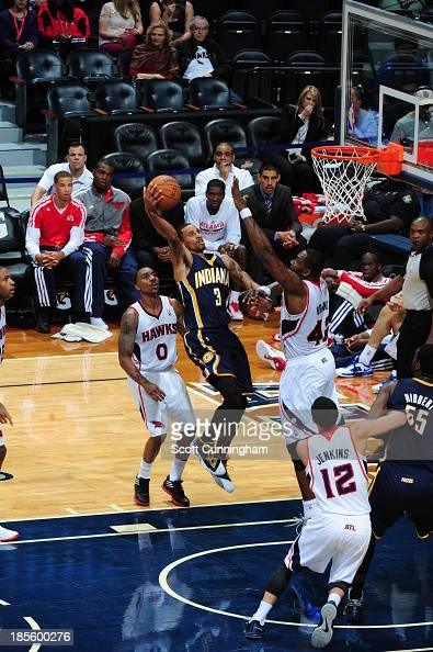 George Hill of the Indiana Pacers shoots the ball against Jeff Teague and Elton Brand of the Atlanta Hawks on October 22 2013 at Philips Arena in...