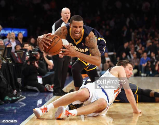 George Hill of the Indiana Pacers trips over Beno Udrih of the New York Knicks at Madison Square Garden on November 20 2013 in New York City NOTE TO...