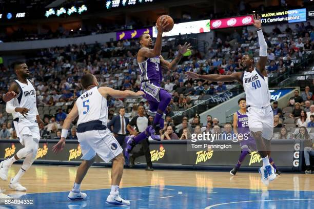George Hill of the Sacramento Kings drives to the basket against JJ Barea of the Dallas Mavericks and Harrison Barnes of the Dallas Mavericks in the...