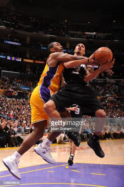 George Hill of the San Antonio Spurs is fouled by Ron Artest of the Los Angeles Lakers at Staples Center on February 3 2011 in Los Angeles California...