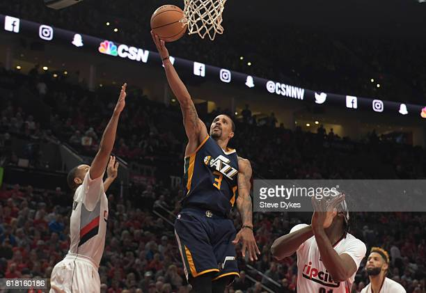 George Hill of the Utah Jazz drives to the basket on CJ McCollum and Noah Vonleh of the Portland Trail Blazers in the third quarter of an NBA game at...