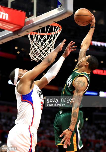 George Hill of the Utah Jazz dunks over Paul Pierce of the Los Angeles Clippers during the second half of Game Seven of the Western Conference...