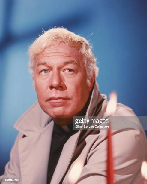 George Kennedy US actor wearing a mackintosh raincoat with the collar up in a studio portrait against a blue background circa 1980