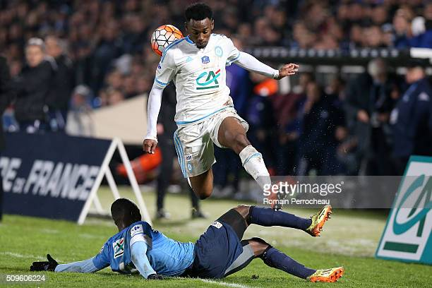 George Kevin Nkoudou of Olympique de Marseille is tackled by Ange Negus Gnaleko of Trelissac FC during the French Cup match between Trelissac FC and...