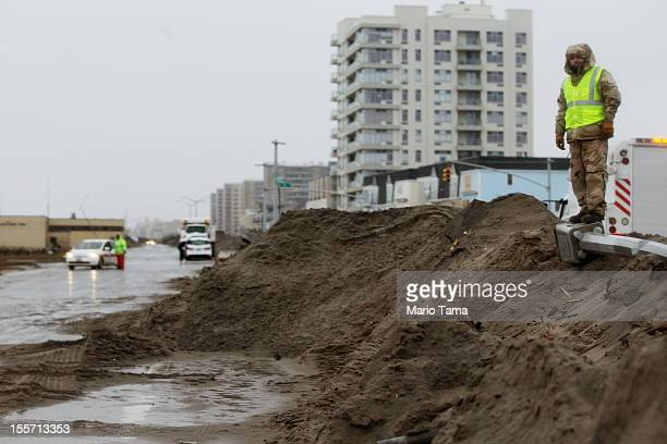 George Kroenert of the city Parks Department stands on a pile of sand collected from the streets as crews attempt to clear the streets of sand and...