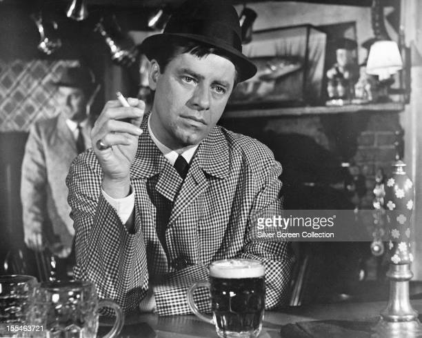 George Lester played by American actor and comedian Jerry Lewis has a pint of beer and a cigarette in a London pub in 'Don't Raise The Bridge Lower...