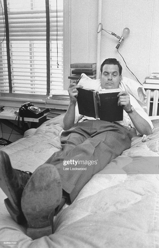 George Lincoln Rockwell, head of the American Nazi Party, reclining on his bed at headquarters reading Mein Kampf.