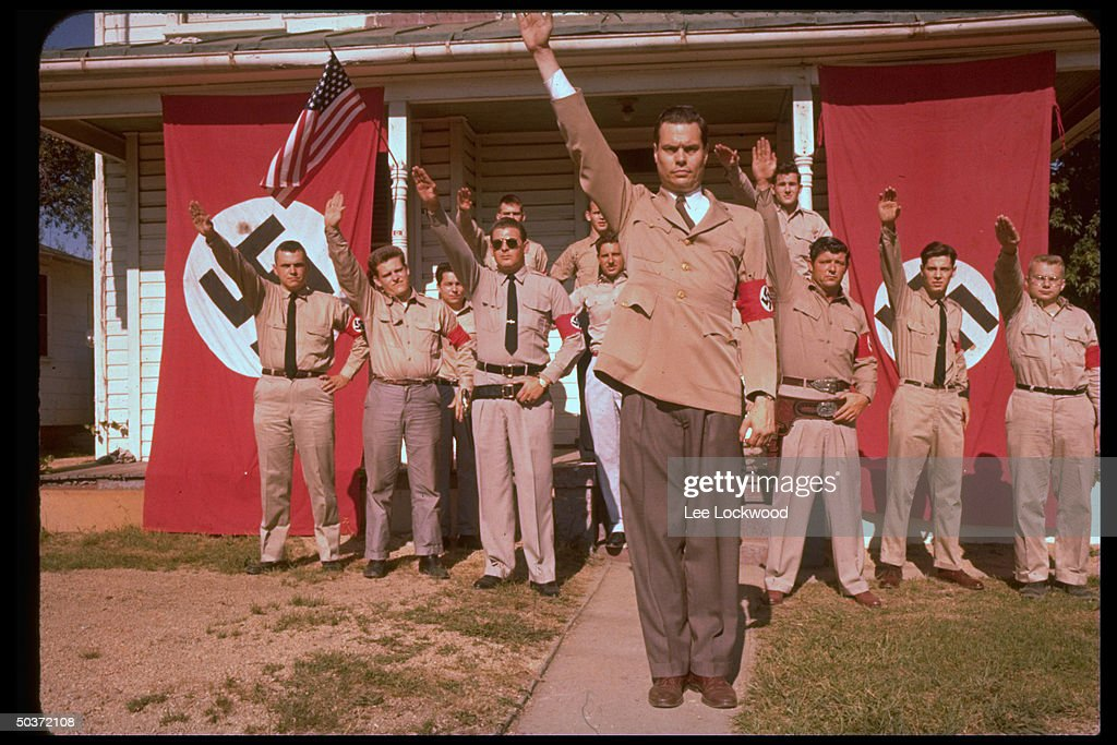George Lincoln Rockwell (C), self-styled head of the American Nazi Party, standing with group of followers in uniform with Nazi and American flags waving in bkgrd. giving Party salute.