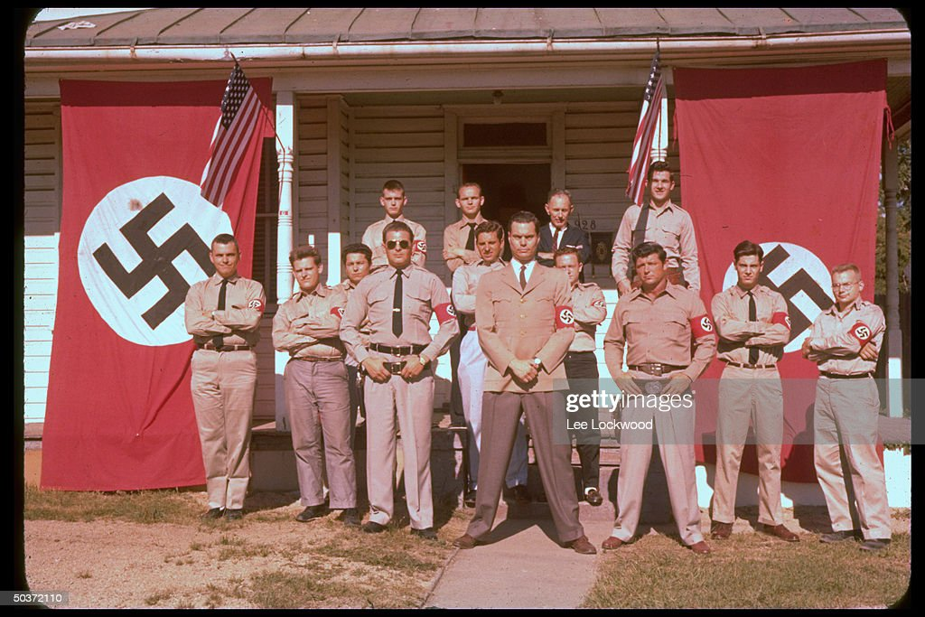 George Lincoln Rockwell (C), self-styled head of the American Nazi Party, standing with group of followers in uniform with Nazi and American flags waving in bkgrd.