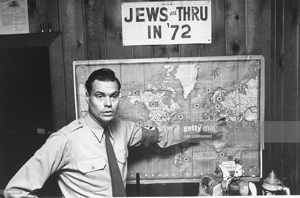George Lincoln Rockwell, self-styled head of the American Nazi Party, standing before a world map studded with Swastikas under sign reading: JEWS ARE THRU IN '72.